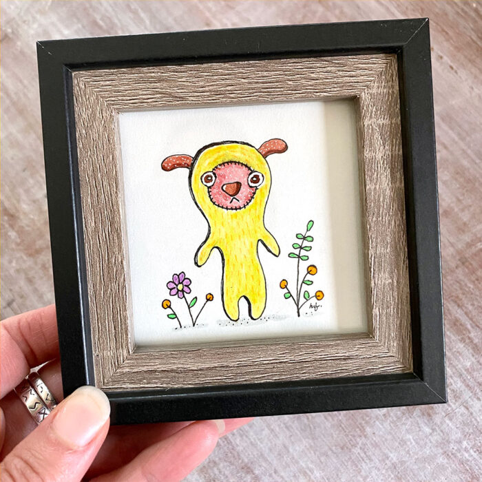 Small framed mixed media drawing of cute yellow creature with pink face standing in flowers