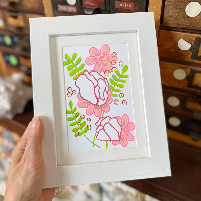 3.5x5.5 drawing in white frame of deep pink and peach flowers with green ferns on white paper.